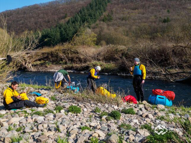 Vier Personen machen Paddelpause auf einer Kiesbank am Flussufer