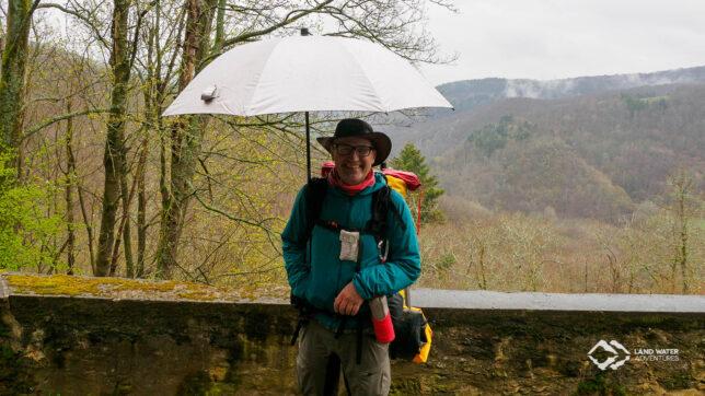 Eine Person steht mit Regenschirm und großem Rucksack bepackt vor einer Mauer, im Hintergrund das Hahnenbachtal