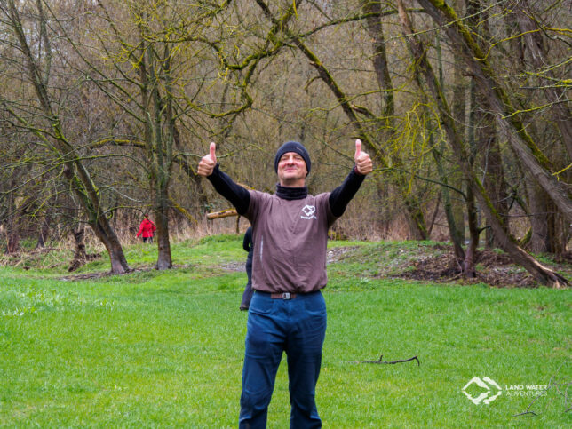 Eine Person auf einer Wiese stehend, lachend beide Daumen in die Luft haltend