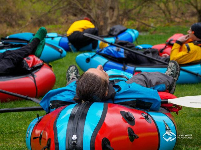 Eine Person liegt auf einem Packraft auf einer Wiese und ruht sich aus. Im Hintergrund weitere Boote.