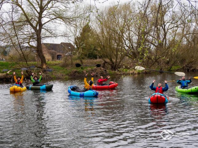 Sechs Personen in bunten Packrafts auf dem Fluss werfen freudig strahlend ihre Paddel in die Luft.