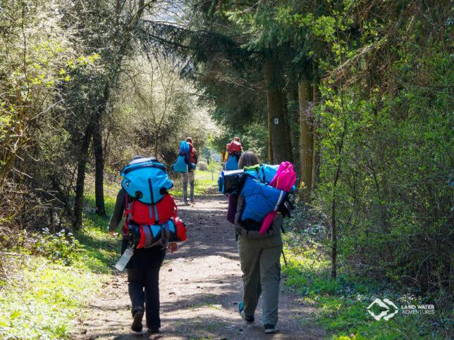 Mehrere Personen mit großen, bepackten Rucksäcken wandern einen schmalen Weg entlang, es ist Frühling.