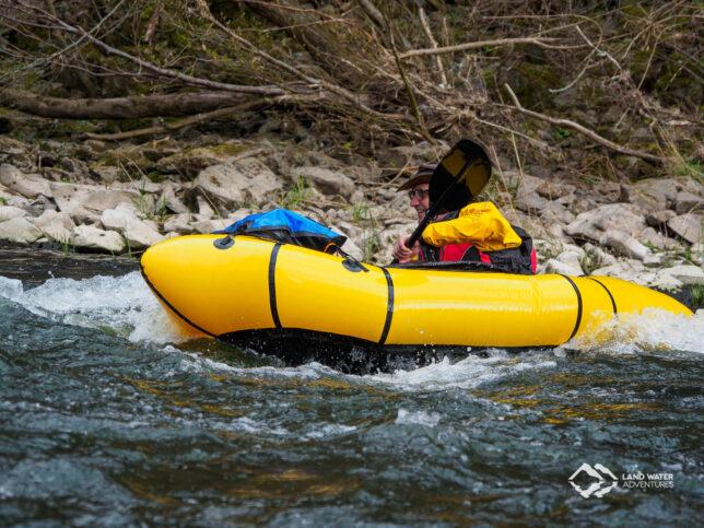 Eine Person mit Hut in einem gelben Packraft geht in die Welle der Nahe